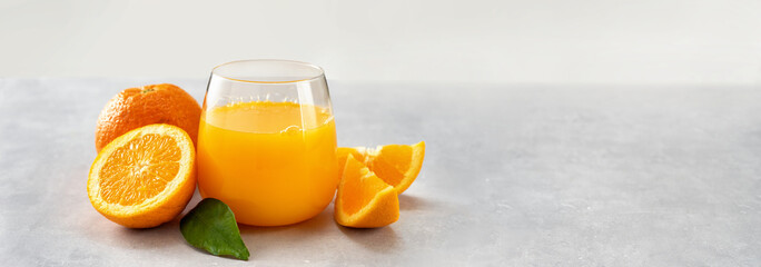 Fresh orange juice glass and oranges on light background