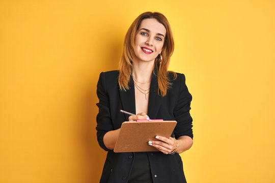 Redhead business caucasian woman holding clipboard over isolated background with a happy face standing and smiling with a confident smile showing teeth