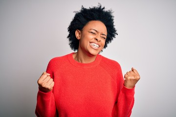Young beautiful African American afro woman with curly hair wearing red casual sweater very happy...