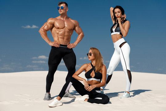 Sporty fitness models in sportswear. Athletic man and women in leggings outdoor
