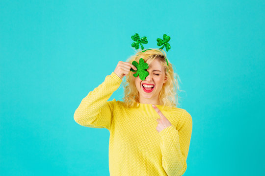 Studio portrait of a smiling woman holding shamrock covering one eye having fun, with St. Patrick's Day head decoration