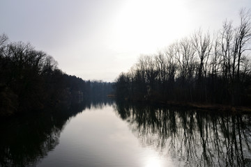 Fluss mit gespiegelter Baumsilhouette