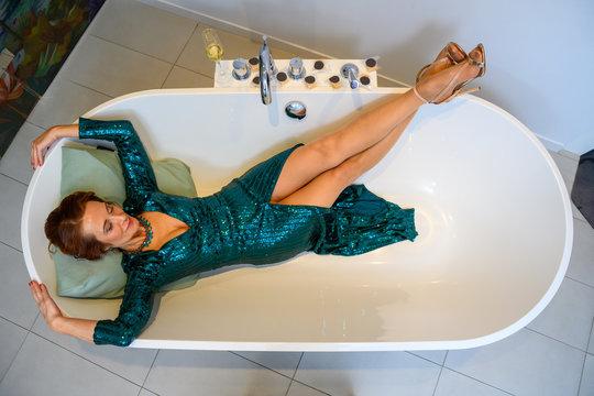Frau liegt mit Abendkleid in freistehender Badewanne