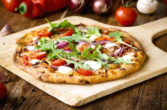 Freshly baked pizza with arugula, tomato, red onion and mozzarella