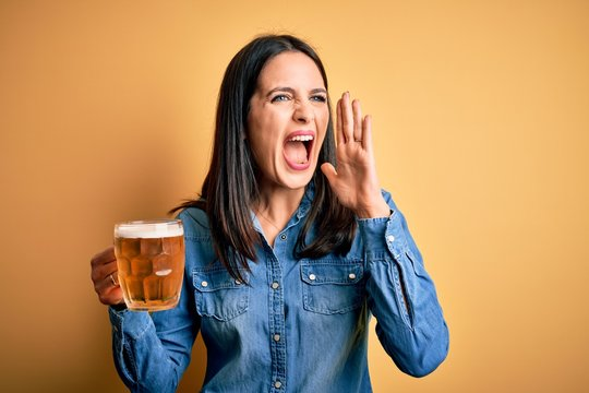Young woman with blue eyes drinking jar of beer standing over isolated yellow background shouting and screaming loud to side with hand on mouth. Communication concept.