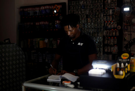 An assistant at a locksmith store uses LED lights to continue working during an electricity load shedding blackout in Waterfall
