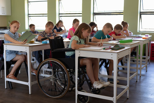 Group of schoolchildren sitting at desks in an elementary school classroom