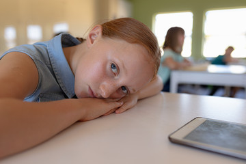 Schoolgirl leaning on her desk in an elementary school classroom