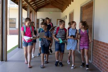 group of school pupils walking in an outdoor corridor at elementary school