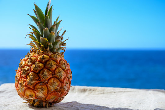 Exotic fruits, fresh ripe sweet pinapple, blue sea and tropical food background