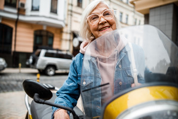 Cheerful aged woman riding motorcycle stock photo