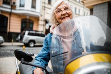 Cheerful aged woman riding motorcycle stock photo Fotobehang
