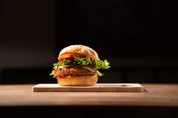 home made hamburger made by white sesame bun, tomato slice, salad, cheese, grilled meat and onion on wooden tray wooden table with dark isolate background stock photo