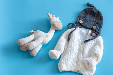 Knitted baby clothes and accessories on a blue background .