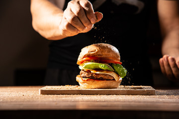 home made hamburger made by white sesame bun, tomato slice, salad, cheese, grilled meat and onion on wooden tray wooden table with cooking decorate chef hand in dark isolate background stock photo
