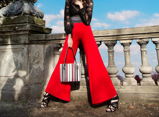 Wall Mural - Woman with red wide pants holding the handbag purse on the bridge. Fashion shoot