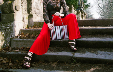 Wall Mural - Woman sitting on the stairs with red pants, black shoes and purse bag. Fashion image.