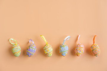 Colorful easter eggs on orange background with copy space, Top view