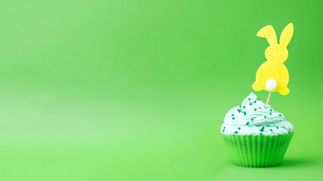 Cream cupcake with topper silhouette of easter bunny isolated on green background. Easter food concept sweets, greeting card banner for Easter. Copy space