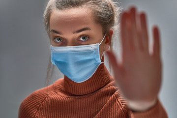 Stop the virus and epidemic diseases. Healthy woman in blue medical protective mask showing gesture...