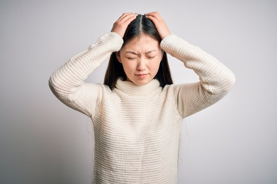 Young beautiful asian woman wearing casual sweater standing over isolated background suffering from headache desperate and stressed because pain and migraine. Hands on head.