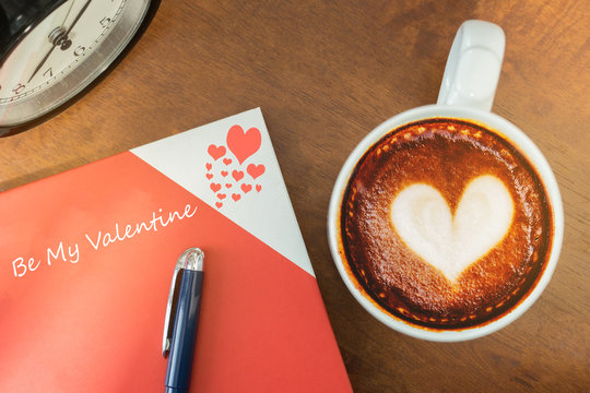 Be my valentine book with coffee latte art love symbol.