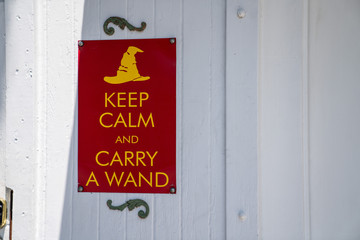 Keep calm and carry a wand gag humor sign hanging on wall