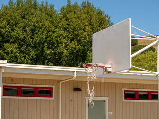 White basketball hoop with faded hoop and backboard at school