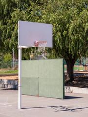 Short basketball hoop at public grade school playground recess area