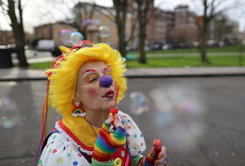 Clown blows bubbles before an annual service of remembrance in honour of British clown Joseph Grimaldi, at the All Saints Church in Haggerston