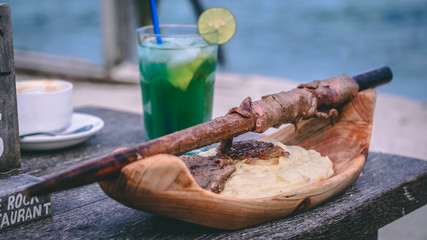 Foto auf Leinwand Sansibar Pingwe, Zanzibar, Tanzania 30.12.2019 - Beef with potatoes in The Rock restaurant with a cocktail in the background