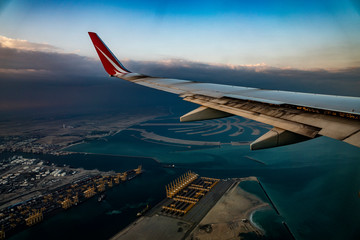 travel, in, Dubai, vacation, flight, on, plane, altitude, sky, view, in, porthole, wing, plane, sunrise, clouds, sun, rays, light, dawn, beauty, Persian, Gulf, water, buildings, land, panorama
