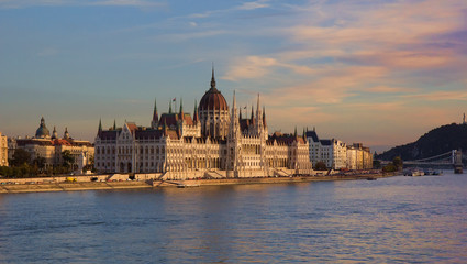 Neo-gothic Hungarian Parliament Building in the Pest side of Budapest and on the banks of River Danube at sunset.