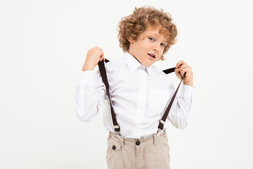 Charming boy with curly hair in white shirt with black suspenders stands isolated on white...
