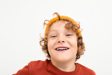 Portrait of charming boy with curly hair, yellow hat smiles isolated on white background
