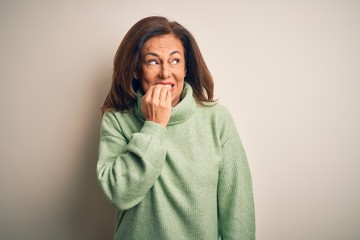 Middle age beautiful woman wearing casual turtleneck sweater over isolated white background looking stressed and nervous with hands on mouth biting nails. Anxiety problem.