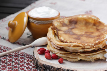 Concept of Russian cuisine. Pancakes with sour cream and strawberries on a wooden background. Copy space