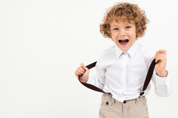 Charming boy with curly hair in white shirt with black suspenders stands isolated on white background