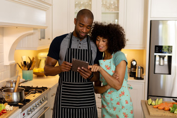 Happy young couple wearing apron and using tablet computer