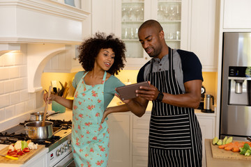 Happy young couple cooking and using tablet computer in the kitchen