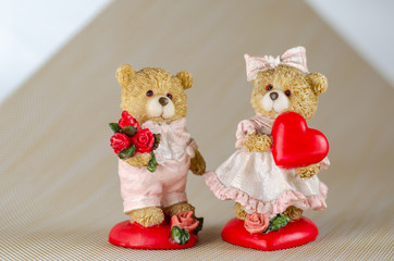 Two figures of lovers cubs on a light background. Bear holds heart, bear a bouquet of flowers for a loved one. Eye level shooting. Selective focus. Close-up.