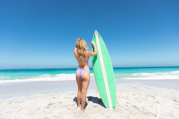 Young woman with surfboard at the beach