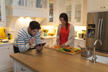 Young couple using tablet computer while cooking