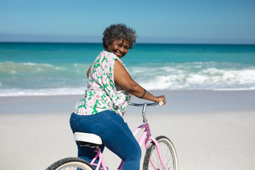 Old woman with a bike at the beach