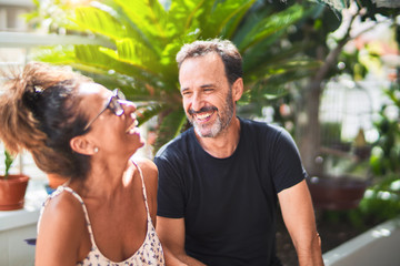 Middle age beautiful couple sitting on terrace speaking and smiling