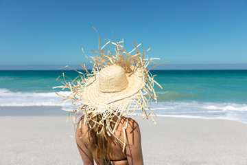 Rear view young woman with straw hat