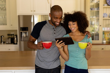 Happy young couple using tablet computer in the kitchen