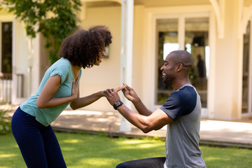 Young man doing marriage proposal in the garden