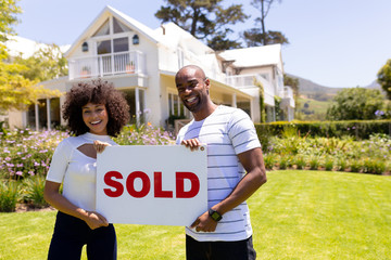 Happy young couple in the garden holding sold sign