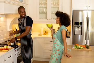 Happy young couple cooking and wearing apron in the kitchen